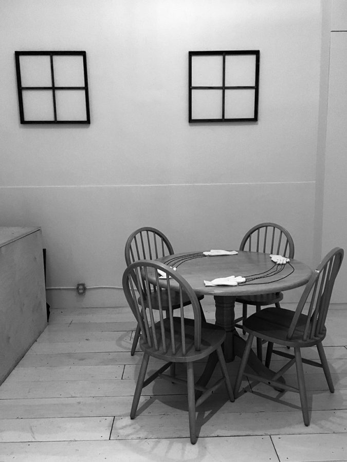 A black and white image depicting a small room with a circular table and four wooden chairs with pieces of paper.