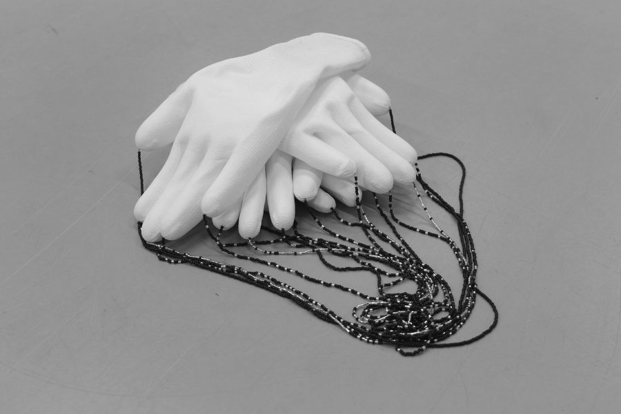 Black and white image of four gloves layered over one another, alternating as if in a relaxed gesture, with a string of small beads casting out from the fingers.