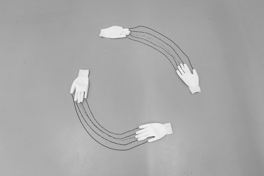 A black and white image of two pairs of white gloves lay on the floor, fingers pointing toward the other with strings of beads connecting them from the fingers. the formation of the gloves and beads form a circle.