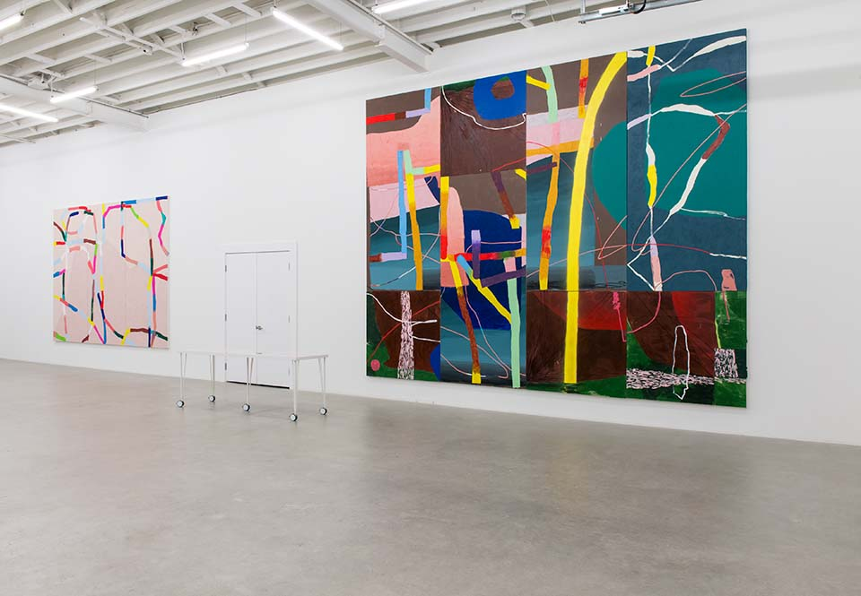 Installation of a bright art gallery with two very large abstract paintings on the wall. They make use of contrasting colours and directional lines.