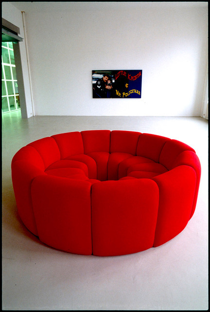 Coloured, red couches turn inwards to form a closed circle.