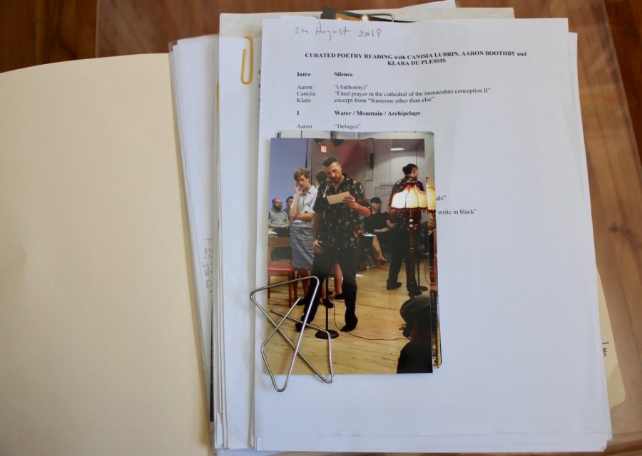 Coloured, script with pictures of a poetry performance attached.