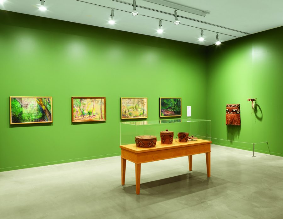 An installation view of the VAG with green walls featuring paintings on the walls and a vitrine with woven baskets inside in the centre of the room.
