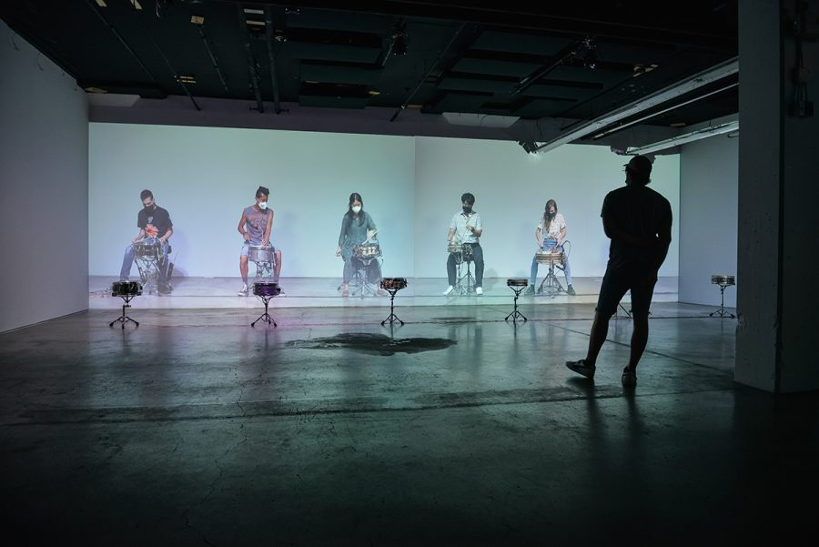 A dark gallery space features a wall with two projected screens depicting six seated performers playing snare drums. A viewer stands in front of the video and appears as a dark cameo.